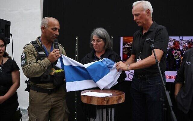 العقيد في الجيش الإسرائيلي غولان فاخ (الثاني إلى اليسار) يقدم علم إسرائيل، الذي وقّع عليه عناصر وحدة الإنقاذ الوطنية التابعة للجيش الإسرائيلي إلى عمدة مقاطعة ميامي، ديد دانييلا ليفين كافا (وسط) وعمدة سيرفسايد، تشارلز بوركيت (على يمين الصورة) في 10 يوليو، 2021 في سيرفسايد، فلوريدا.  (Anna Moneymaker/Getty Images/AFP (Photo by Anna Moneymaker / GETTY IMAGES NORTH AMERICA / Getty Images via AFP)