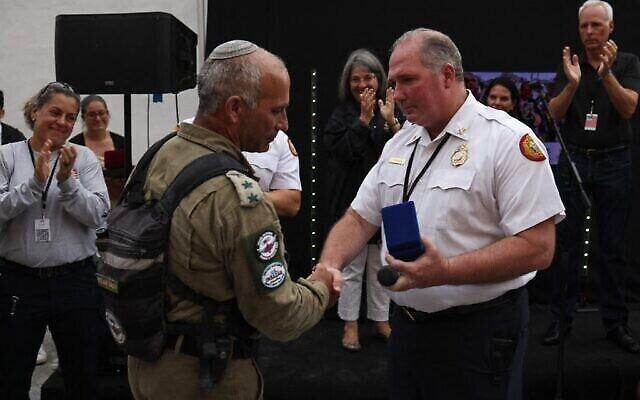 رئيس إدارة إطفاء ميامي ديد، آلان كومينسكي، على يسار الصورة، يقدم ميدالية للعقيد غولان فاخ، قائد وحدة الإنقاذ الوطنية في الجيش الإسرائيلي خلال حفل وداع في 10 يوليو، 2021، في سيرفسايد، فلوريدا. (Anna Moneymaker / GETTY IMAGES NORTH AMERICA / Getty Images via AFP)