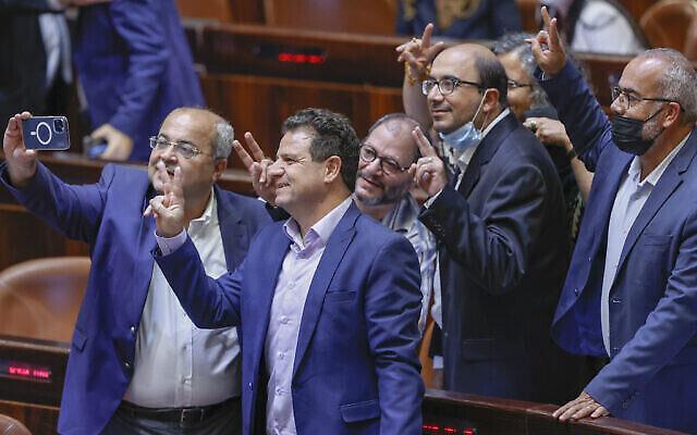 """أعضاء الكنيست من """"القائمة المشتركة"""" يحتفلون بعد تصويت الكنيست على رفض تمديد قانون لم شمل العائلات الفلسطينية، في القدس، 6 يوليو، 2021. (Yonatan Sindel / Flash90)"""