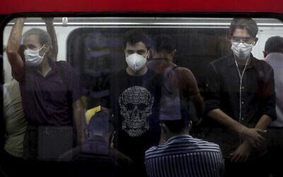 توضيحية: أشخاص يرتدون الكمامات للوقاية من فيروس كورونا يقفون داخل قطار في طهران، إيران، 8 يوليو، 2020. (AP / Ebrahim Noroozi)