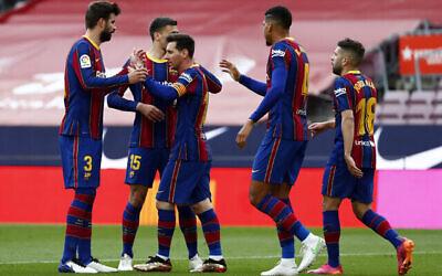 لاعب برشلونة ليونيل ميسي يحتفل مع زملائه بتسجيل الهدف الافتتاحي خلال مباراة الدوري الاسباني لكرة القدم بين نادي برشلونة وسيلتا فيغو في ملعب كامب نو في برشلونة، إسبانيا، 16 مايو، 2021. (AP Photo / Joan Monfort)