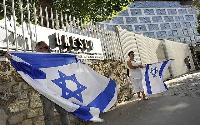 يهوديان فرنسيان يرفعون العلم الإسرائيلي خلال مشاركتهما في مظاهرة مناهضة لليونسكو ، بالقرب من مقر الوكالة الثقافية في باريس، 17 يوليو، 2017. (Serge Attal / Flash90)