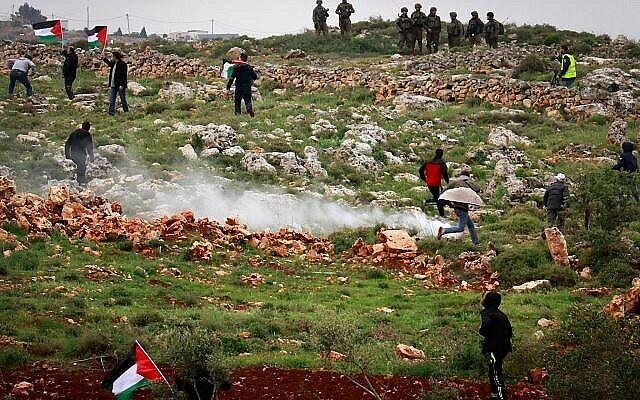 توضيحية: متظاهرون فلسطينيون يشتبكون مع القوات الإسرائيلية خلال مظاهرة بمناسبة ذكرى 'يوم الأرض'، في قرية قصرة في الضفة الغربية، 30 مارس، 2018. (Nasser Ishtayeh / Flash90)