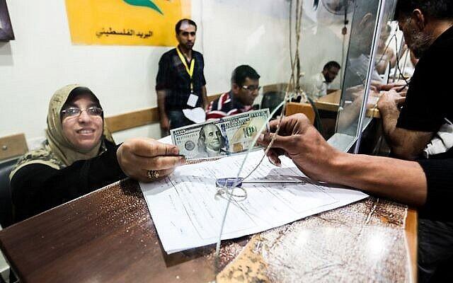 الفلسطينيون يتلقون مساعداتهم المالية كجزء من الأموال التي خصصتها قطر في مكتب بريد في مدينة غزة، 19 مايو، 2019. (Abed Rahim Khatib / Flash90)