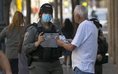 عناصر من شرطة حرس الحدود يقدمون كمامةلرجل في شارع يافا وسط مدينة القدس، 7 أكتوبر، 2020، خلال إغلاق فرضته السلطات بسبب جائحة كورونا في جميع أنحاء البلاد. (Nati Shohat / Flash90)