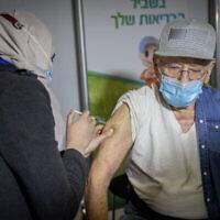 رجل يتلقى حقنة من لقاح كوفيد-19 في مركز التطعيم في القدس، 21 يناير، 2021. (Yonatan Sindel/Flash90)