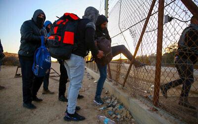 عمال فلسطينيون من مدينة الخليل بالضفة الغربية يحملون متعلقاتهم الشخصية أثناء عبورهم إلى إسرائيل عبر ثقب في السياج الأمني بالقرب من مدينة الخليل بالضفة الغربية، 31 يناير، 2021. (Wisam Hashlamoun / Flash90)