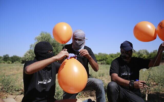 أنصار حركة الجهاد الإسلامي الفلسطينية يعدون بالونات حارقة لإطلاقها باتجاه إسرائيل، شرقي مدينة غزة، 15 يونيو، 2021, (Atia Mohammed / Flash90)