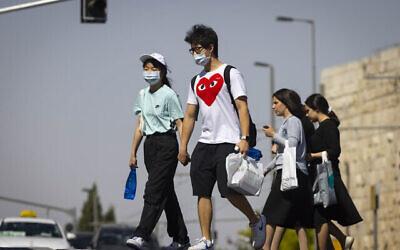 أشخاص يسيرون في شوارع القدس، بعضهم يرتدون الكمامات، 29 يونيو، 2021. (Olivier Fitoussi/Flash90)