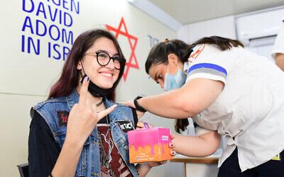 فتاة إسرائيلية تتلقى جرعة من لقاح كورونا في مركز للتطعيم تابع لبلدية تل أبيب ونجمة داوود الحمراء، تل ابيب، 4 يوليو، 2021. (Tomer Neuberg/Flash90)