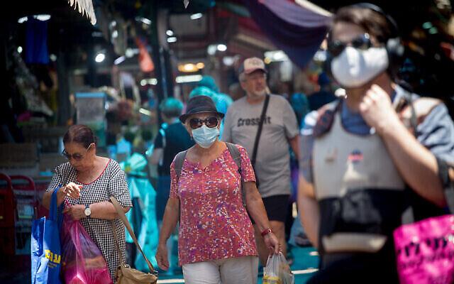 إسرائيليون ، بعضهم يرتدي الكمامات، يسيرون في سوق الكرمل في تل أبيب، 5 يوليو، 2021. (Miriam Alster / Flash90)
