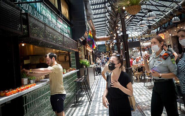 أشخاص يرتدون كمامات للوقاية من فيروس كورونا داخل سوق سارونا في تل أبيب، 13 يوليو، 2021. (Miriam Alster / FLASH90)