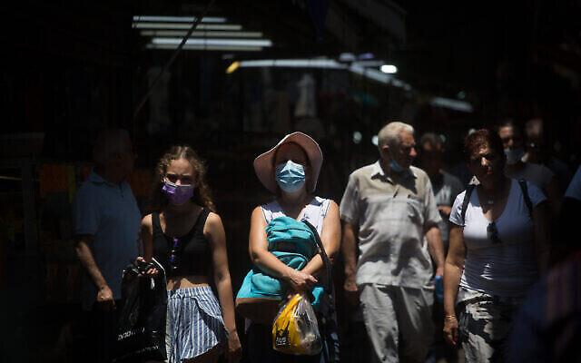 إسرائيليون يرتدون الكمامات أثناء سيرهم في سوق الكرمل في تل أبيب، 20 يوليو، 2021. (Miriam Alster / FLASH90)