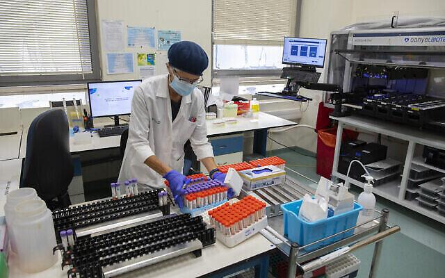 الطاقم الطبي يحلل اختبارات كورونا في مختبر تابع لصندوق المرضى في القدس، 22 يوليو، 2021. (Olivier Fitoussi / Flash90)