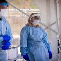 عاملا رعاية صحية يأخذان مسحات لاختبارات فيروس كورونا في القدس، 22 يوليو، 2021. (Yonatan Sindel / Flash90)
