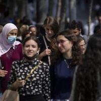 أشخاص ، بعضهم يرتدي الكمامات، يسيرون في شارع يافا في القدس، 25 يوليو، 2021. (Olivier Fitoussi / Flash90)