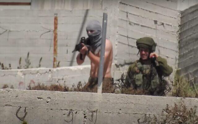 جندي خارج الخدمة بقميص ملفوف حول وجهه كقناع يفتح النار باتجاه قرية عوريف من مستوطنة يتسهار، 14 أيار، 2021.  (B'Tselem)