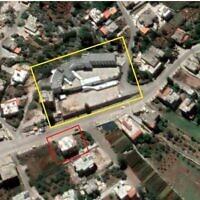 مستودع أسلحة مزعوم لحزب الله (محدد باللون الأحمر) يظهر على الجانب الآخر من الشارع من مدرسة (محدد باللون الأصفر) في بلدة عبا بوسط لبنان في صورة أقمار صناعية من 1 يونيو.(Google Earth, outlines added by The Times of Israel)
