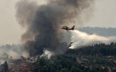 طائرة إطفاء تخمد الحرائق في منطقة قرية كوركولي في شمال إيفيا في اليونان. 4 أغسطس 2021  (Photo by Louisa GOULIAMAKI / AFP)