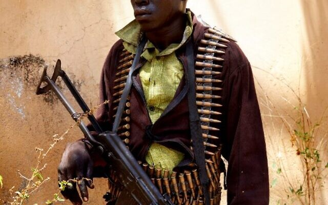 (FILES) In this file photograph taken on February 14, 2019, a member of SPLA-IO stands guard as peace talks take place in Pageri, Imatong State, South Sudan. - Deadly fighting erupted on August 7, 2021, between rival factions of South Sudan Vice President Riek Machar's SPLA-IO, his military spokesman said in a statement. The clashes erupted after Machar's rivals declared this week they had deposed him as the head of the party and its military forces. (Photo by ALEX MCBRIDE / AFP)