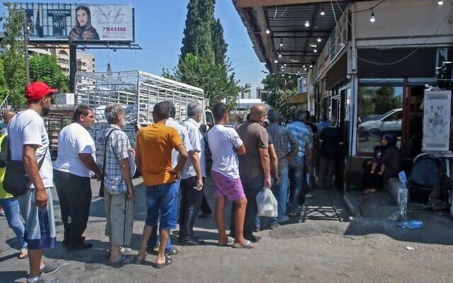 طابور من المواطنين اللبنانيين الذين يقفون في انتظار الحصول على الخبز أمام مخبز في مدينة صيدا الساحلية الجنوبية، في 13 أغسطس 2021، وسط أزمة اقتصادية متفاقمة أدت إلى نقص مختلف في المواد الغذائية الأساسية في البلاد.