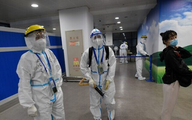 عمال يرتدون ملابس واقية كإجراء احترازي ضد فيروس كورون يقومون بتطهير منطقة ينتظر فيها المسافرون الدوليون الوافدون ليتم نقلهم إلى فندق الحجر الصحي في مطار بودونغ في شنغهاي في 13 أغسطس 2021. ( GREG BAKER / AFP)