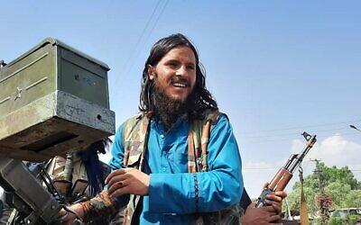 مقاتل من طالبان يقف على متن مركبة في أحد شوارع ولاية لغمان، 15 أغسطس، 2021. (AFP)