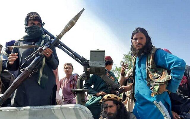 مقاتلو طالبان يجلسون فوق سيارة في شارع في ولاية لغمان، 15 أغسطس، 2021. (AFP)