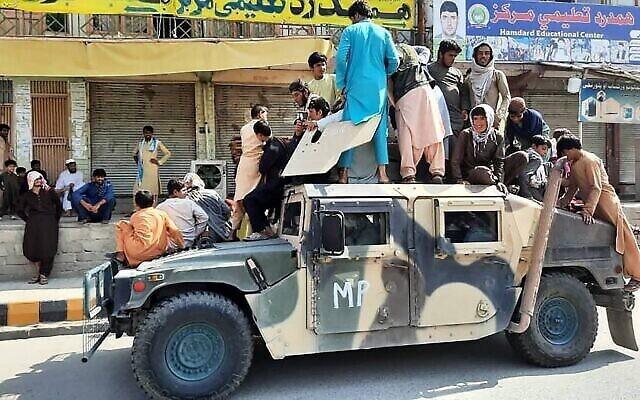 مقاتلو طالبان والسكان المحليون يجلسون على عربة همفي تابعة للجيش الوطني الأفغاني على جانب الطريق في ولاية لغمان، 15 أغسطس 2021 (AFP)