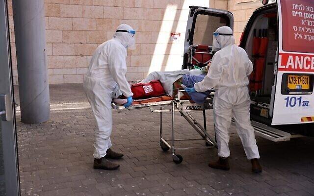 مسعفون في نجمة داود الحمراء ينقلون مريضا بفيروس كورونا إلى مستشفى هداسا عين كارم في القدس بسبب وصول المستشفيات الأخرى إلى السعة الكاملة بعد الزيادة الحادة في عدد الإصابات بفيروس كورونا في إسرائيل، 15 أغسطس، 2021. (Menahem KAHANA / AFP)