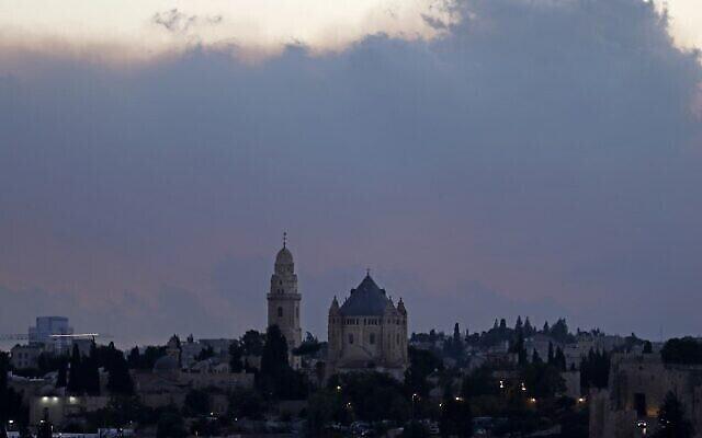 سحابة من الدخان تتصاعد من حريق غابة كبير على مشارف القدس خلف كنيسة رُقاد السيّدة العذراء، 15 أغسطس، 2021. ( Ahmad GHARABLI / AFP)
