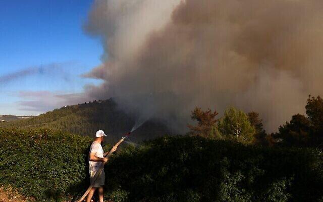 مواطن يرش الماء بخرطوم مع تصاعد دخان كثيف من حريق ضخم في جبال القدس بالقرب من موشاف شورش الإسرائيلي، 15 أغسطس، 2021. (Menahem KAHANA / AFP)