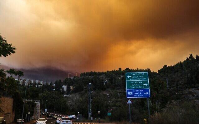 سيارات تسير على طريق مع تصاعد ألسنة اللهب والدخان جراء حريق ضخم في جبال القدس بالقرب من قرية شورش الإسرائيلية، 15 أغسطس، 2021.  (Menahem KAHANA / AFP)