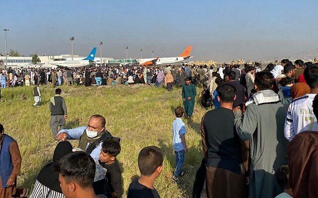 مواطنون أفغان يحتشدون في المطار خلال انتظارهم للمغادرة من كابول، 16 أغسطس، 2021. (Shakib Rahmani / AFP)
