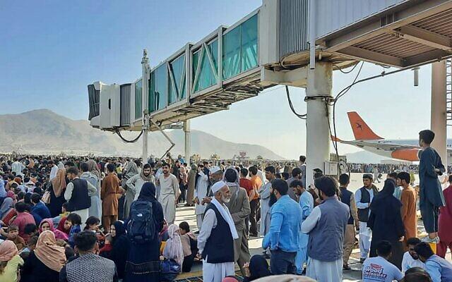 مواطنون أفغان يحتشدون في مدرج مطار كابول في 16 أغسطس 2021، للفرار من البلاد بعد سيطرة طالبان على أفغانستان وفرار الرئيس أشرف غني من البلاد وإقراره بانتصار المتمردين في الحرب التي استمرت 20 عاما. (AFP)