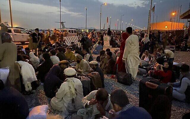 أفغان ينتظرون لكوب طائرة عسكرية أمريكية لمغادرة أفغانستان، في المطار العسكري في كابول في 19 أغسطس 2021 بعد استيلاء طالبان العسكري على أفغانستان. (Shakib RAHMANI / AFP)