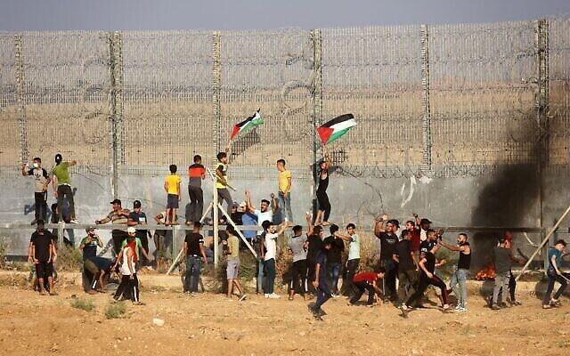 متظاهرون فلسطينيون يرفعون الأعلام الفلسطينية يحرقون الإطارات خلال مظاهرة عند السياج الحدودي مع إسرائيل ، شرقي مدينة غزة، 21 أغسطس، 2021. (Said Khatib / AFP)