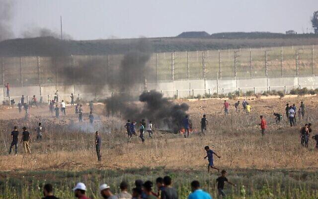 متظاهرون فلسطينيون يحرقون الإطارات وسط اشتباكات مع قوات الأمن الإسرائيلية في أعقاب مظاهرة عند السياج الحدودي مع إسرائيل، شرقي مدينة غزة، في 21 أغسطس، 2021. (SAID KHATIB / AFP)