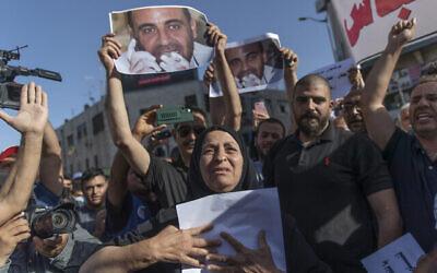 مريم بنات(67 عاما) والدة الناقد للسلطة الفلسطينية نزار بنات، تحمل ملصقا يحمل صورته في مسيرة احتجاجية على وفاته، في مدينة رام الله بالضفة الغربية، 3 يوليو، 2021. (AP Photo / Nasser Nasser)