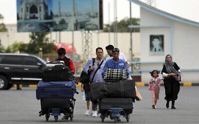مسافرون يسيرون إلى صالة المغادرة بمطار حامد كرزاي الدولي في كابول، أفغانستان، 14 أغسطس، 2021. (AP Photo / Rahmat Gul)