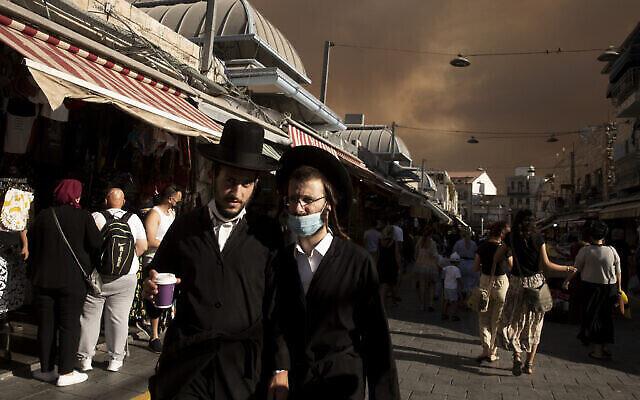 يهود حريديم يسيرون في سوق محاني يهودا تحت سماء مظلمة بسبب الحرائق القريبة، في القدس، 15 أغسطس، 2021. (AP Photo / Maya Alleruzzo)