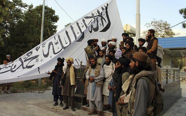مقاتلو طالبان يقفون لالتقاط صورة أثناء رفع علم الحركة في منزل حاكم مقاطعة غزنة، في غزنة، جنوب شرق أفغانستان، 15 أغسطس، 2021. (AP Photo / Gulabuddin Amiri)