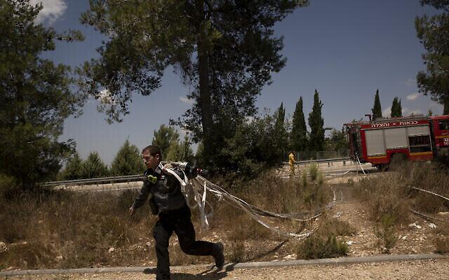 رجل إطفاء إسرائيلي أول يركض بخراطيم مياه خلال محاولات إخماد حريق لليوم الثاني بالقرب من شورش، في ضواحي القدس، 16 أغسطس، 2021. (AP Photo / Maya Alleruzzo)