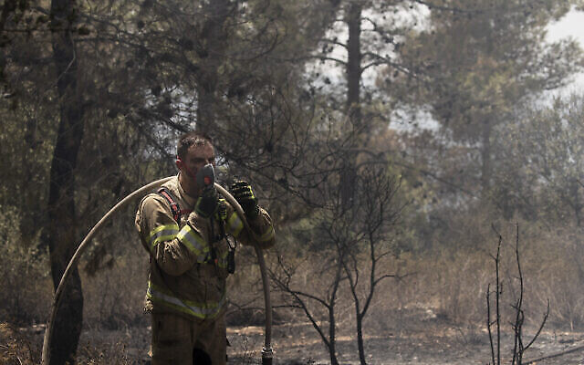 رجل إطفاء إسرائيلي يتوقف ليرتدي قناعا خلال مكافحته للحريق لليوم الثاني بالقرب من شورش، في ضواحي القدس، 16 أغسطس، 2021. (AP Photo / Maya Alleruzzo)