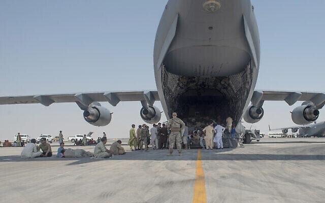 """في هذه الصورة التي قدمتها القوات الجوية الأمريكية، ينتظر الأشخاص الذين تم إجلاؤهم تحت جناح  طائرة """"سي-17 غلوب ماستر 3"""" بعد وصولهم إلى مكان لم يكشف عنه في منطقة الشرق الأوسط يوم الجمعة 20 أغسطس 2021، بعد إجلائهم على متن طائرة عسكرية من مطار حامد كرزاي الدولي في كابول ، أفغانستان ، كجزء من عملية """"إجلاء الحلفاء"""". (Airman 1st Class Kylie Barrow, U.S. Air Force via AP)"""