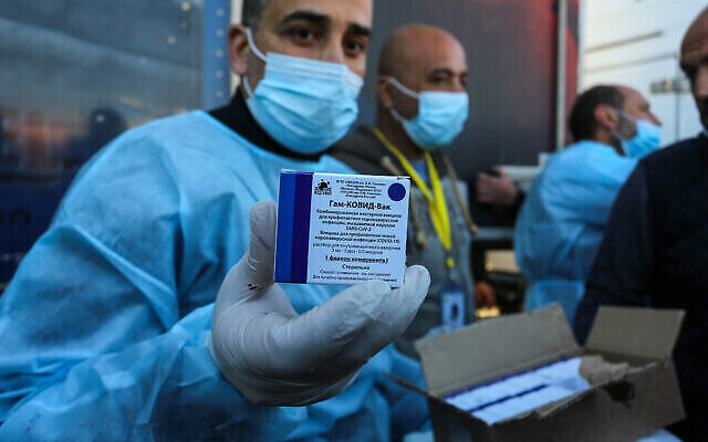 فلسطينيون من وزارة الصحة يتلقون شحنة من جرعات لقاح فيروس كورونا Sputnik V الروسي مرسلة من الإمارات العربية المتحدة، بعد أن سمحت السلطات المصرية بدخولها غزة عبر معبر رفح جنوب قطاع غزة، 21 شباط، 2021. (Abed Rahim Khatib/Flash90)
