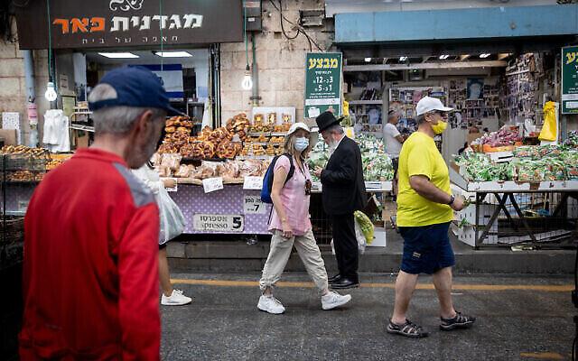 توضيحية: أشخاص يرتدون الكمامات في سوق محانيه يهودا في القدس، 15 يونيو، 2021. (Yonatan Sindel / Flash90)