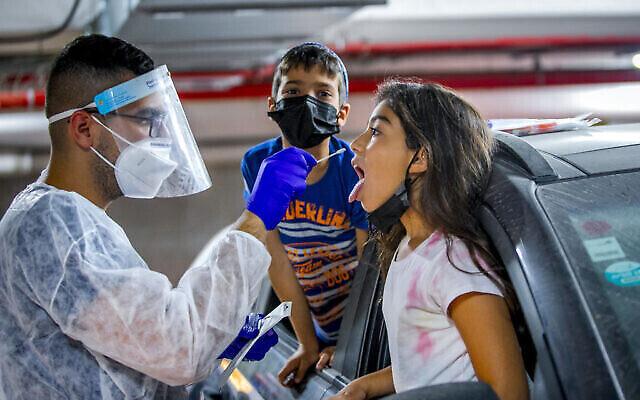 """عامل في مجال الرعاية الصحية يأخذ عينات اختبار لطفلة إسرائيلية في محطة """"افحص وسافر"""" تابعة لصندوق المرضى """"مكابي""""للتحقق من عدم إصابتها بفيروس كورونا، في موديعين، 15 أغسطس، 2021. (Yossi Aloni / Flash90)"""