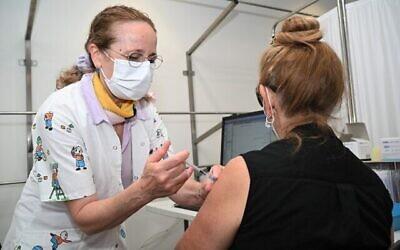 امرأة إسرائيلية تتلقى جرعة معززة من لقاح فيروس كورونا في منشأة خدمات الرعاية الصحية في كلاليت في بلدة كاتسرين في مرتفعات الجولان، 16 أغسطس، 2021 (Michael Giladi / Flash90)