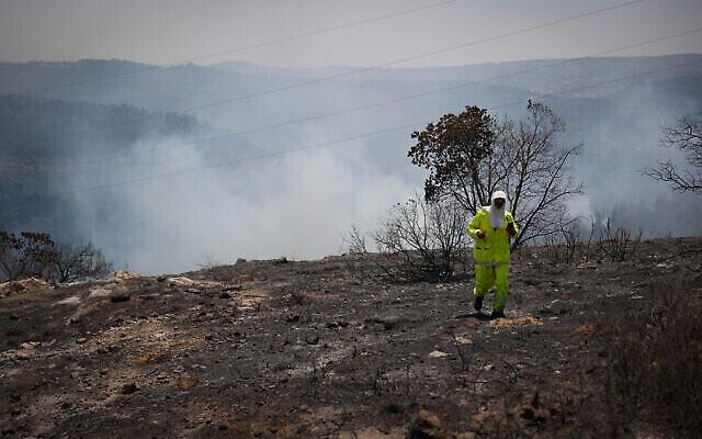 رجل إطفاء يعمل على إخماد حريق كبير بالقرب من بيت مئير ، 16 أغسطس، 2021. (Yonatan Sindel / Flash90)